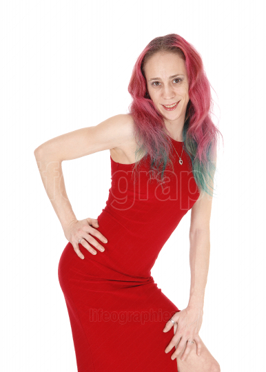 Young woman in red dress and red hair bending