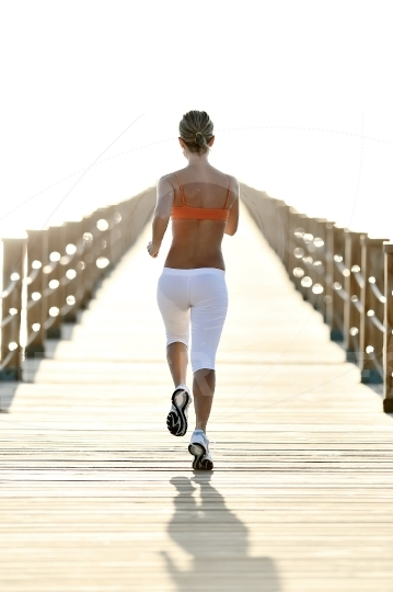 Young woman jogging on wooden bridge by the sea