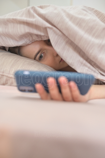 Young Woman Lies Under A Blanket With A Phone In Her Hands