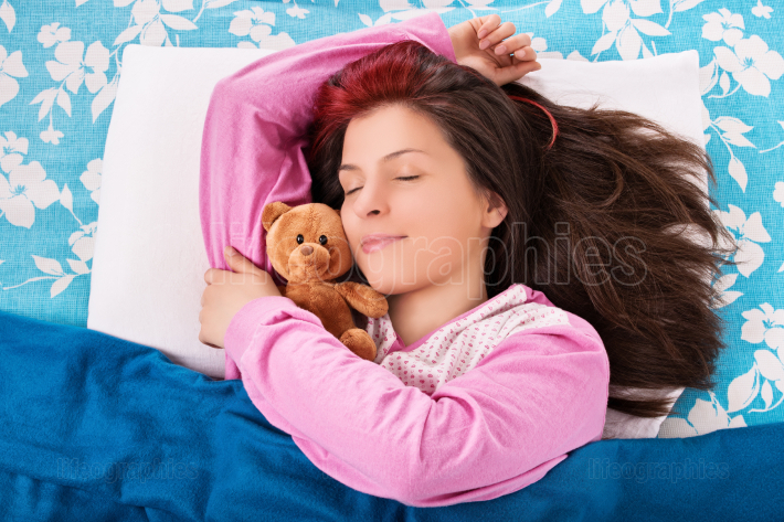 Young woman sleeping and hugging her teddy bear