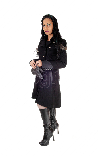 Young woman standing in black coat and boots