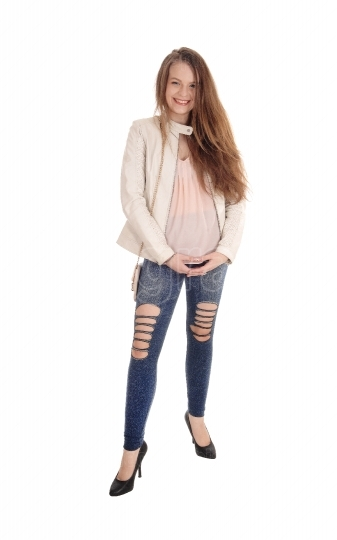 Young woman standing in jeans and jacket