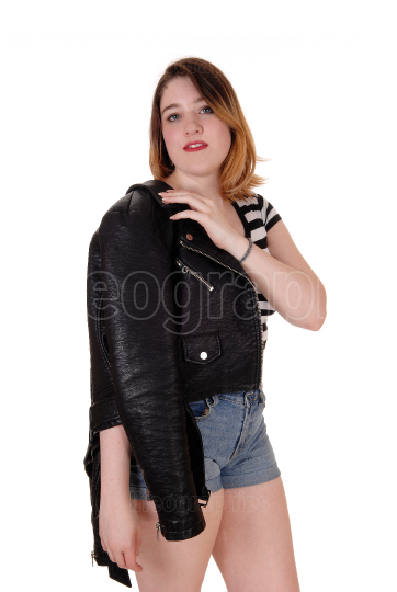 Young woman standing in shorts with jacket over shoulder