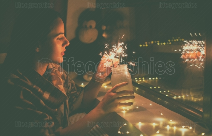 Young woman who lights fireworks at home