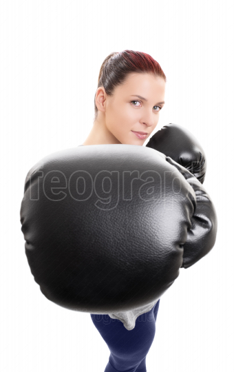 Young woman with boxing gloves punching the camera