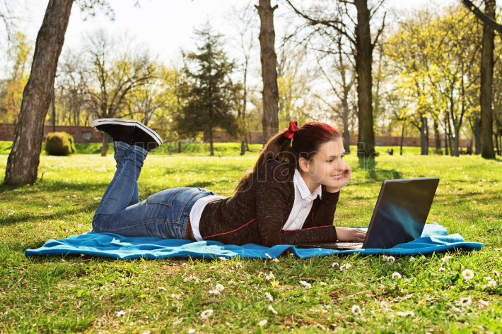 Young woman working on her laptop in a park